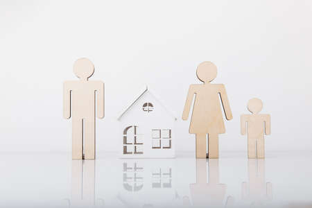 Small model of house and family isolated on white background