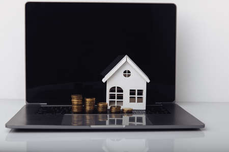 House model, laptop and coins. Mortgage concept