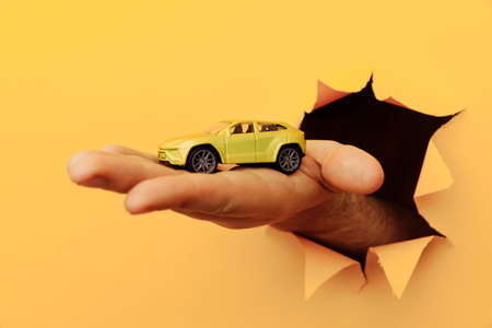 Male hand with house car through a rip in yellow paper wall. Sale and rent concept 版權商用圖片