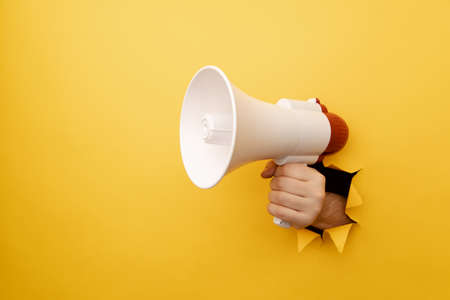 Male arm hold megaphone isolated through torn yellow background
