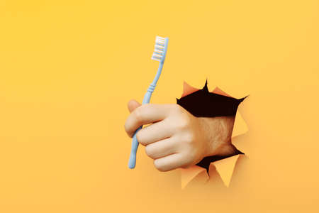 Anonymous hand holding toothbrush outstretched in hole of torn paper