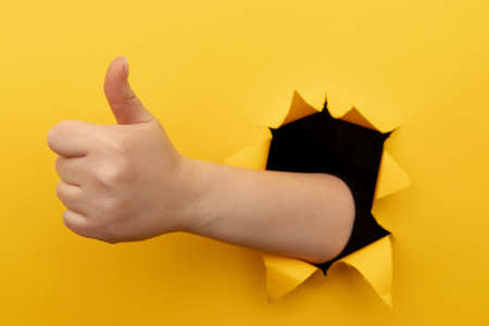 Female hand showing a thumb up sign through a ripped hole in yellow paper wall. Well done, good job concept 版權商用圖片
