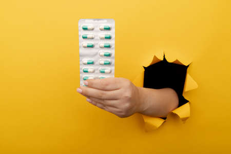 Female hand showing a blister of pills out of a hole torn in yellow paper wall. Health care, pharmaceutics and medicine advertisement