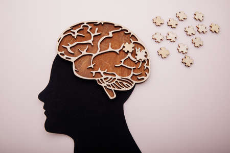 Head of man with brain and wooden puzzle. Alzheimers disease, dementia and mental health concept
