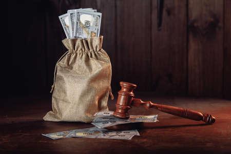 Money bag with dollar banknotes and judges gavel. Litigation, dispute resolution, conflict of interest settlement