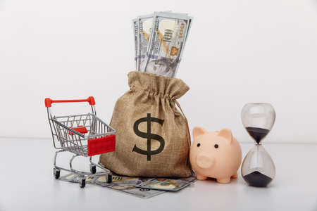 Dollar money bag, ohurglass and a shopping cart on white background
