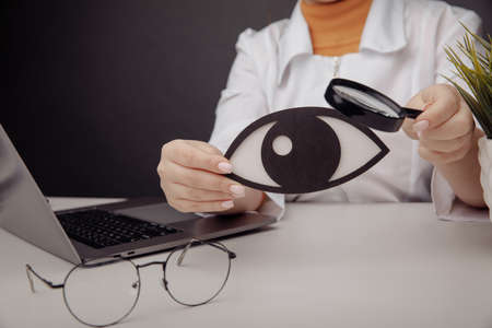 Doctor showing a wooden eye by magnifier. Healthcare concept