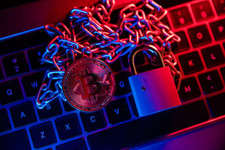 Bitcoin with chain and padlock. Conceptual photography of financial fraud