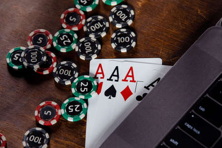 Online casino concept. Playing chips and cards on a wooden background