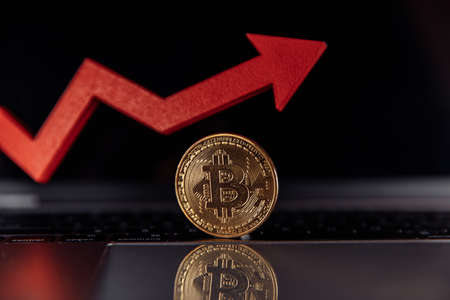 Bitcoin and red growth arrow close-up. Ð¡ryptocurrency value concept