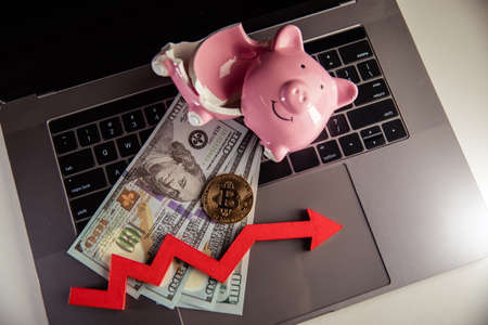Gold bitcoin, broken piggy bank and arrow down on laptop. The fall in the value of bitcoin and investment concept