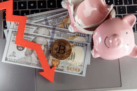 Bitcoin, broken piggy bank and arrow down on dollar cash. Cryptocurrency and investment theme