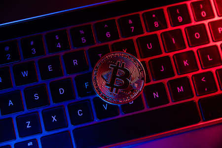 Bitcoin coin in neon on laptops keyboard. Cryptocurrency investment concept