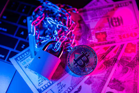 Bitcoin with chain and padlock on dollar cash. Conceptual photography of financial fraud