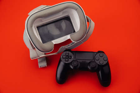 VR virtual reality glasses with back gamepad on red background