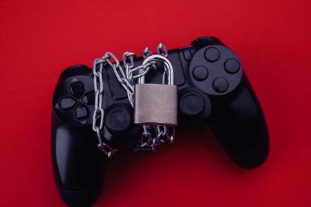 Gamepad with padlock, game addiction concept Фото со стока