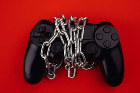 Game addiction concept. Gamepad is tied by chain