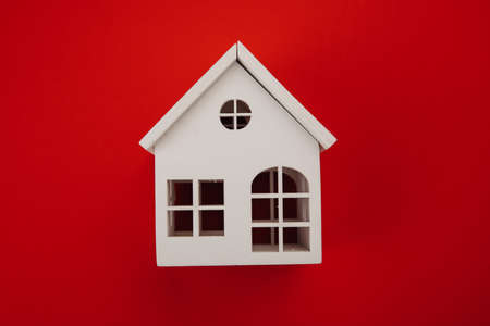 White model of house isolated on red.