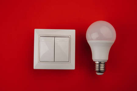 Light bulb and white switch on red background