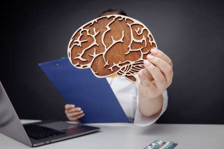 Healthcare and treatment concept. Doctor showing wooden brain close-up