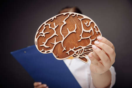 Doctor holding wooden brain close-up. The importance of early diagnosis concept