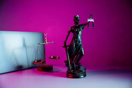 Bronze statue Lady Justice holding scales and sword in notary office