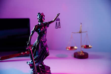 Law concept. Bronze statue Lady Justice holding scales and sword in notary office Фото со стока