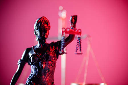 Statue of Lady Justice in notary office in red neon. Symbol of justice and law.