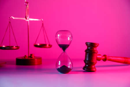 Hourglass, scales and wooden judge gavel in pink neon