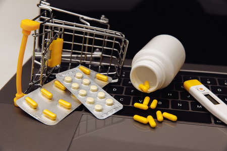 Drugs in trolley and medical tools on laptop, concept of online shopping