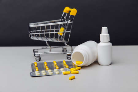 Shopping cart with compounded prescription medications shipped from a mail order pharmacy on a grey background Фото со стока