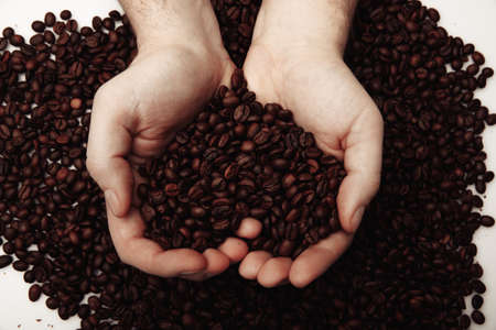 Coffee beans in man palms in form of a heart on coffee background