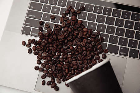 A cup of coffee on keyboard and coffee beans. Top view Фото со стока