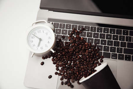 A cup of coffee on keyboard, alarm clock and coffee beans. Top view Фото со стока
