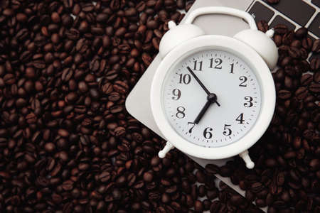White alarm clock and coffee beans on keyboard. Morning workplace concept