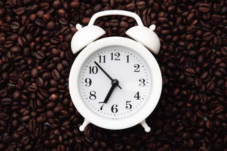 Alarm clock on coffee bean background