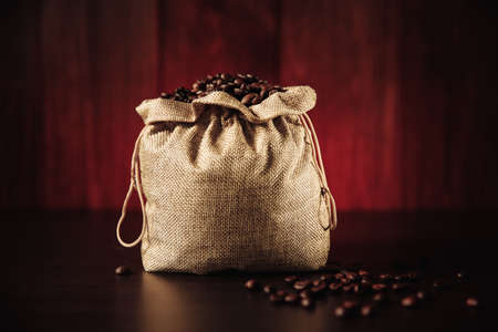 Black coffee beans in bag on wooden background