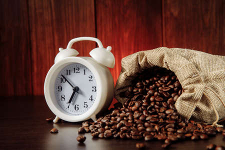 A white alarm clock and coffee beans in a sack bag Фото со стока