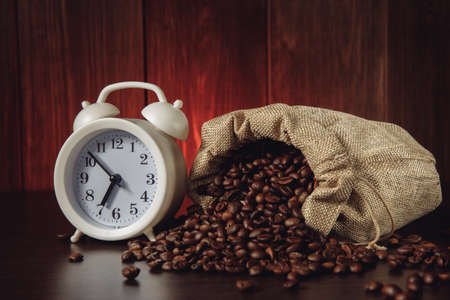 Alarm clock and coffee beans in a sack bag