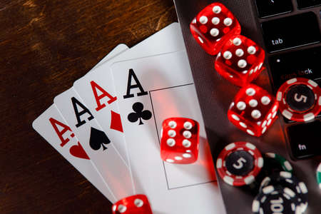Online gambling concept. Red playing dice, chips and cards on a wooden desk
