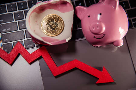 Bitcoin, broken piggy bank and arrow down on laptop. Cryptocurrency. The fall in the value of bitcoin