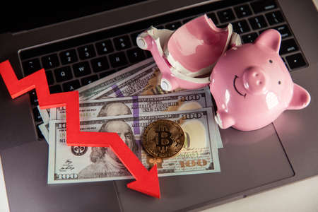 Bitcoin, broken piggy bnak and arrow down close-up. Cryptocurrency and investment concept. Фото со стока