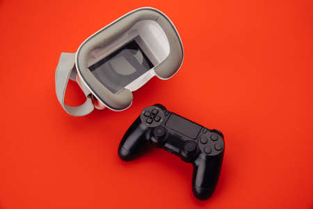 Cybersport concept. VR virtual reality glasses with back gamepad on red background
