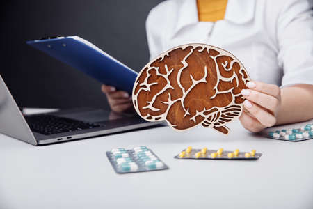Healthcare and treatment concept. Doctor holding wooden model of the brain.