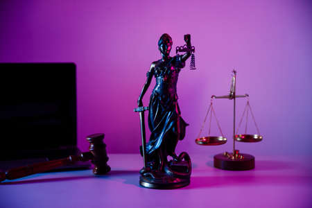 Bronze statue Lady Justice with scales in notary office on purple background