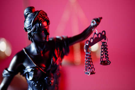 Judgment and law concept. Figure of Lady Justice on red background