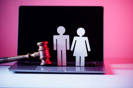Wooden figure in shape of people and gavel on the table. Family law concept Фото со стока