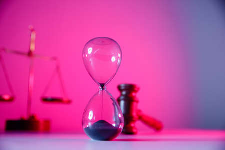 Law and justice concept, Hourglass, scales and wooden judge gavel in pink neon close-up