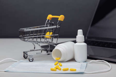 Small shopping cart with medicines. Concept for online purchase of medicines Фото со стока