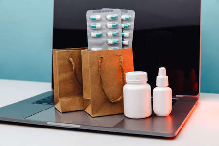 Online pharmacy concept. Paper bags with prescription drugs and pills and white conteiners on laptop